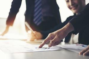hommes d'affaires travaillant et pointant sur un diagramme financier graphique et des documents d'analyse sur une table de bureau photo
