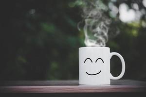 tasses heureuses sur table en bois avec bokeh photo