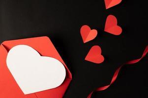 des coeurs blancs et des coeurs rouges en papier sont placés sur un fond noir. photo