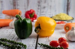poivrons, poivrons frais, tomates, ail et carottes sur un fond en bois blanc. photo