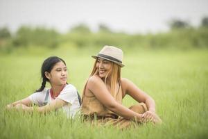 Heureuse mère avec sa fille assise sur le parc de terrain en herbe photo
