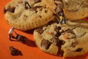 personnes en plastique travaillant sur des cookies aux pépites de chocolat photo