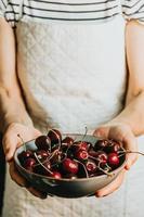 vieille serveuse offre et tient un bouquet de cerises dans un plat, fruits, vie saine, bonne alimentation, concepts méditerranéens, espace de copie, image verticale photo