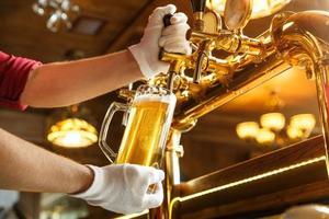 mains de barman versant de la bière légère dans un verre photo