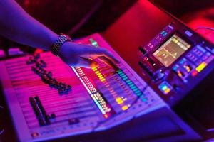 ingénieur du son travaillant avec des équipements de sonorisation de concert - console de mixage audio avec boutons rétroéclairés. photo