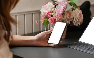 photo recadrée d'une femme tenant un smartphone à la main avec un ordinateur portable sur le bureau au bureau à domicile.