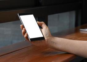 main féminine tenant un écran blanc de smartphone, prise de vue en gros plan. photo