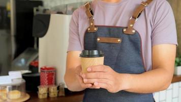 le barista tient une tasse de café à emporter envoyée aux clients. photo