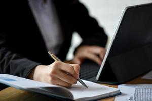 le personnel de bureau utilise un ordinateur portable et note dans un ordinateur portable sur le bureau du bureau. photo