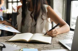 concept d'entreprise, les femmes cadres vérifient les données des graphiques et prennent des notes. photo