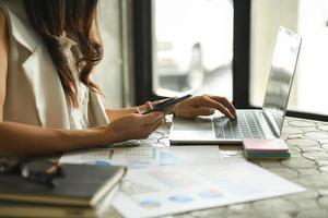 les femmes d'affaires vérifient le tableau des performances de l'entreprise. photo