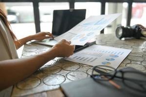 la main d'une femme d'affaires utilise un ordinateur portable pour trouver des informations. Elle tient le graphique et met sa main sur le clavier de l'ordinateur portable. photo