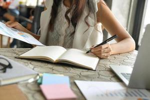 les femmes d'affaires vérifient les données des graphiques et prennent des notes dans un cahier. photo