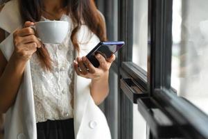 une femme cadre boit du café et utilise un smartphone pendant la pause. elle se tenait près de la fenêtre du bureau. photo