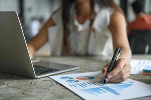 la main d'une femme d'affaires tient un stylo pointant sur le graphique et utilise un ordinateur portable. photo