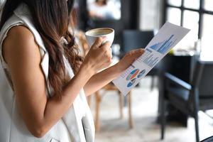 les femmes cadres boivent du café et tiennent des graphiques à portée de main. elle se tenait dans le bureau. photo