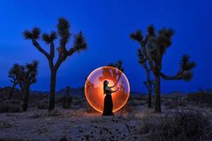 posant une fille peinte de lumière dans les arbres du désert de joshua tree photo
