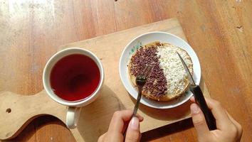une photo de quelqu'un mangeant un mini martabak et buvant une tasse de thé sur une table en bois