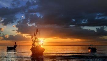 bateaux de pêche silhouette au coucher du soleil. photo