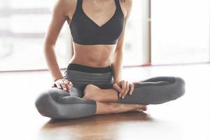 gros plan d'une jeune femme sportive pratiquant le yoga est assise dans le lotus. photo