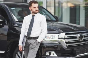 portrait d'un bel homme en vêtements d'affaires debout à l'extérieur du bureau. photo