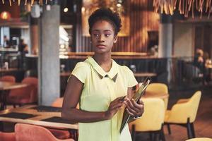 femme d'affaires afro-américaine se tient avec un dossier dans ses mains photo
