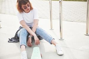 une photo d'une belle fille avec de beaux cheveux tient une planche à roulettes sur une longue planche, regardant la caméra et souriante, la vie urbaine.