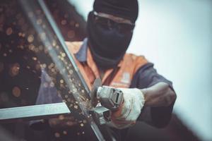 les ouvriers coupent des fermes de toit en acier dans la construction. photo