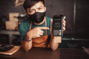 le caissier recommande de payer avec une machine à carte de crédit. photo