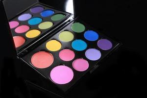 palette colorée de divers fards à paupières sur fond noir photo