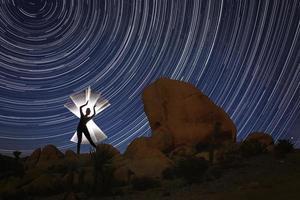 beau modèle éclairé par un tube lumineux avec des traînées d'étoiles du nord dans l'arbre de joshua photo