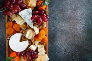 grand plateau de fromages avec assortiment d'apéritifs. raisin, fromage, noix, confiture et pain. photo