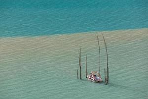 bateau eau turquoise du lac de montagne inondé arbres photo