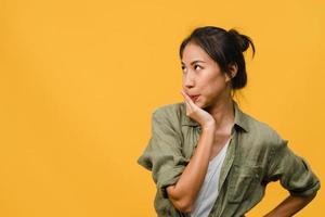 portrait d'une jeune femme asiatique avec une expression négative, des cris excités, des pleurs émotionnels en colère dans des vêtements décontractés isolés sur fond jaune avec un espace de copie vierge. concept d'expression faciale. photo