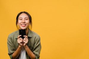 surpris une jeune femme asiatique utilisant un téléphone portable avec une expression positive, un large sourire, vêtue de vêtements décontractés et regardant la caméra sur fond jaune. heureuse adorable femme heureuse se réjouit du succès. photo