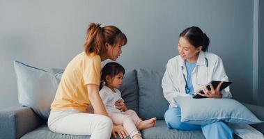 jeune médecin pédiatre asiatique et petite fille patiente utilisant une tablette numérique partageant de bonnes nouvelles sur les tests de santé avec une maman heureuse s'asseoir sur un canapé dans la maison. assurance médicale, rendre visite au patient à domicile concept. photo