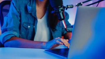 Happy asia girl host record podcast utiliser un microphone porter un casque avec un ordinateur portable interviewer une conversation d'invité pour le contenu dans son home studio la nuit. concept d'équipement sonore. concept de créateur de contenu. photo