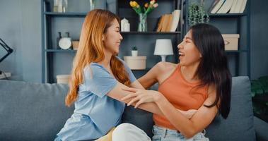 une adolescente asiatique heureuse rend visite à ses amis proches en souriant à la maison. Les meilleurs copains ravis et excités s'embrassent, se saluent avec succès, un véritable concept d'amitié forte. photo