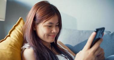 Jeune fille heureuse d'Asie avec un temps de détente utiliser un smartphone s'amuser à bavarder avec des amis de l'université dans le salon à la maison. isoler le mode de vie de l'activité, concept de pandémie de coronavirus à distance sociale. photo