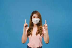 jeune fille asiatique portant un masque médical montre quelque chose dans un espace vide avec vêtue d'un tissu décontracté et regardant la caméra isolée sur fond bleu. distanciation sociale, quarantaine pour le virus corona. photo