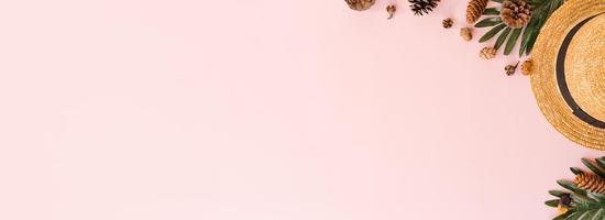 mise à plat créative de vacances de voyage mode tropicale de printemps ou d'été. accessoires de plage vue de dessus sur fond de couleur rose pastel. bannière panoramique avec espace de copie pour le texte et la zone publicitaire. photo