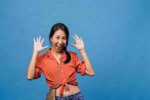 la jeune femme asiatique ressent le bonheur avec une expression positive, une surprise joyeuse et funky, vêtue d'un tissu décontracté et regardant la caméra isolée sur fond bleu. heureuse adorable femme heureuse se réjouit du succès. photo