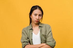 jeune femme asiatique avec une expression négative, hurlant d'excitation, pleurant émotionnellement en colère dans des vêtements décontractés et regarde la caméra isolée sur fond jaune avec un espace de copie vierge. concept d'expression faciale photo