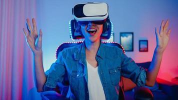 Une fille asiatique heureuse porte des lunettes de réalité virtuelle, des lunettes de protection, un vrai programme de jeu surprise dans son studio de néon la nuit, une jeune femme touche l'air de l'expérience vr, une activité de quarantaine à domicile. photo