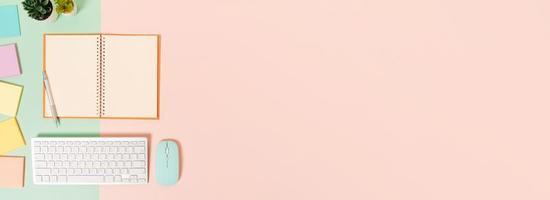 photo créative à plat du bureau de l'espace de travail. bureau vue de dessus avec clavier, souris et cahier noir maquette ouverte sur fond de couleur rose vert pastel. vue de dessus maquette avec copie espace photographie.