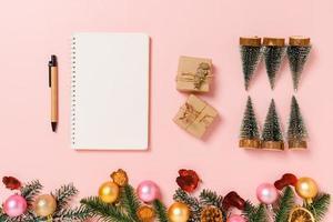 mise à plat créative minimale de la composition traditionnelle de noël d'hiver et de la saison des vacances du nouvel an. vue de dessus ouvrir le cahier noir de maquette pour le texte sur fond rose. maquetter et copier la photographie spatiale. photo