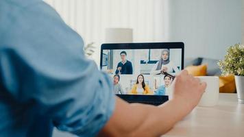un jeune homme d'affaires asiatique utilisant un ordinateur portable parle à ses collègues du plan lors d'une réunion par appel vidéo pendant qu'il travaille à domicile dans le salon. auto-isolement, distanciation sociale, quarantaine pour la prévention du virus corona. photo