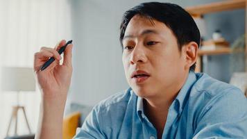 vêtements décontractés pour hommes asiatiques indépendants utilisant un ordinateur portable en ligne dans le salon du bureau à domicile. travail à domicile, travail à distance, enseignement à distance, distanciation sociale, quarantaine pour la prévention du virus corona. photo
