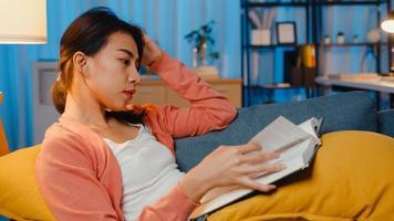 la nuit, une belle dame asiatique a lu un livre avec bonheur dans un salon paisible sur un canapé. éducation à domicile, rester à la maison, activité d'auto-quarantaine, activité amusante pour la quarantaine covid ou coronavirus. photo