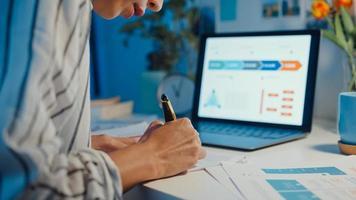 gros plan jeune femme asiatique indépendante se concentrer sur un ordinateur portable écrire une feuille de calcul financière graphique compte plan de marché dans un ordinateur portable et une tablette à la maison. une étudiante apprend en ligne, travaille à partir du concept de nuit à la maison. photo